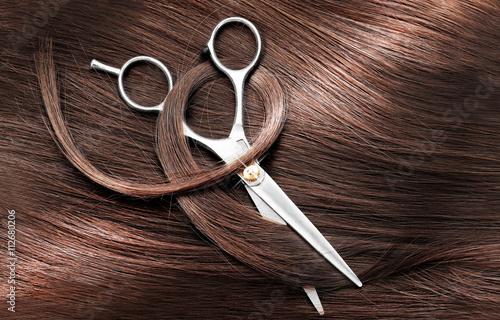 Nożyce fryzjerskie z ciemnobrązowymi włosami, z bliska