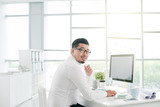Asian software developer working on computer in office