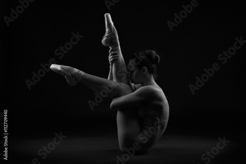 Art nude. Perfect flexible sexy body of young woman on black background - 112709440