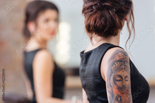 Woman with tattoo on hand standing in front of mirror Poster