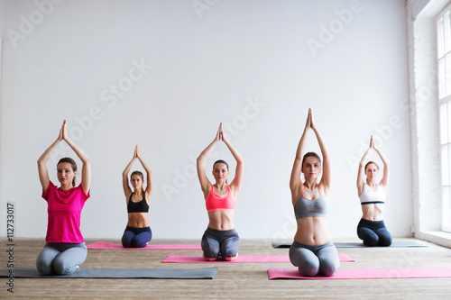Group of people at the gym in a yoga class плакат