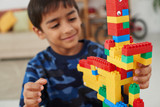 Smiling little boy looking at tower he made out of colorful bricks