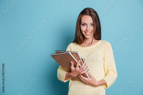 Portrait of beautiful young brunette with notebooks Poster