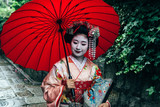 Maiko geisha walking on a street in Kyoto, Japan during a storm with red umbrella