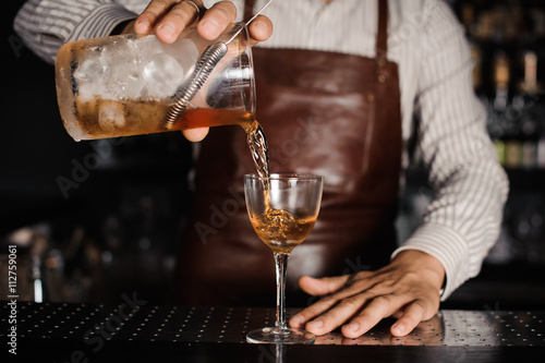 Poster barman pouring alcoholic cocktail in glass