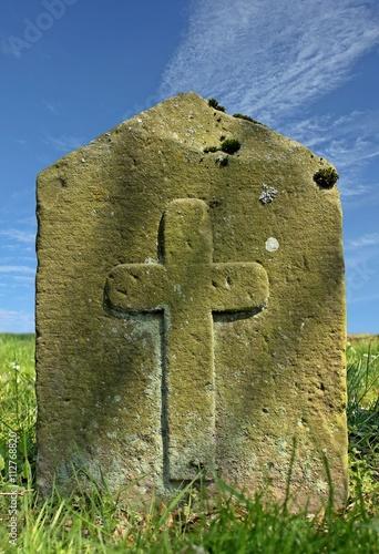 Uralter Grabstein mit Kreuz auf Wiese vor blauem Himmel mit weißen Wolken Poster