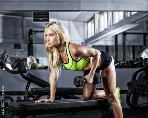 Fototapeta fitness girl exercising with barbell in gym