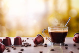 Fototapety Cup of coffee with capsules and bainas and local background