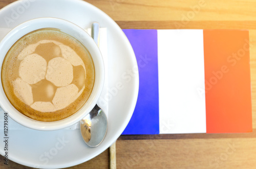 Coffee cup latte art of football ball next flag of France Poster