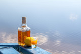 Bottle tequila and shot with lemon on shore of lake