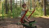 Little boy training on playground equipment in park