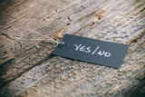"""Closeup of pricing tag with twine and """"Yes/No"""" text on wooden background"""