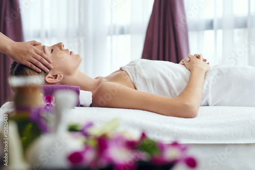 Woman receiving relaxing head massage in spa salon плакат