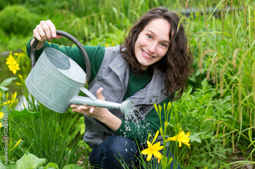 Young attractive woman working in a public garden watering flowe