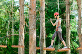 Fototapety adventure climbing high wire park - Young woman on course in mou