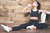 Beautiful woman after fitness exercise drinking natural water