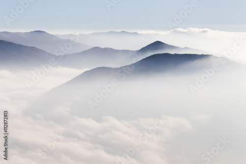 Silhouettes of mountains in the mist - 112872813