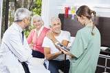Senior Couple Looking At Female Nurse While Sitting By Doctor