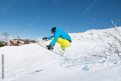 Young man jumping with snowboard Poster