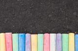 Fototapety Colorful pastel sidewalk chalk on dark asphalt background.