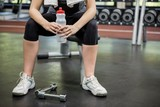 Woman holding a water bottle in gym