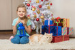 Seven-year girl sits with a cat under the Christmas tree with gifts and smiling happily