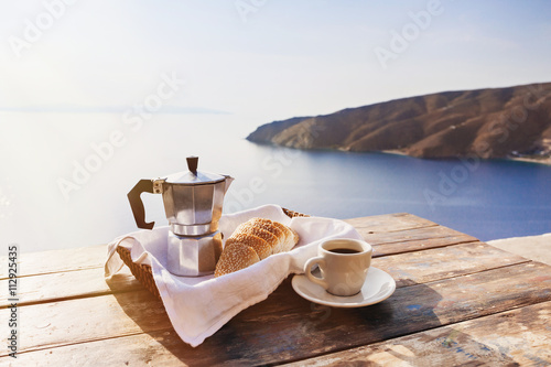 Mediterranean breakfast, cup of coffee and fresh bread on a table with beautiful sea view at the background