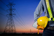 Engineer holding yellow helmet with Transmission tower.