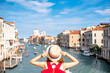 View on Grand canal with woman traveler in hat on Academia bridge in Venice. Back view with copy space