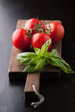Fresh tomatoes and a sprig of basil