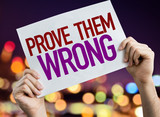 Prove Them Wrong placard with night lights on background