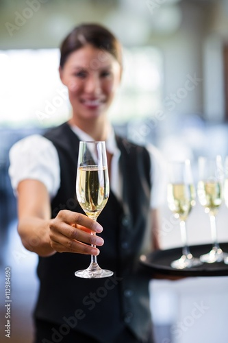 Poster, Tablou Portrait of smiling waitress offering a glass of champagne