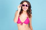Portrait of a happy smiling woman in sunglasses and bikini