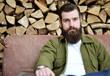 Mann sitzt vor einer Holzwand