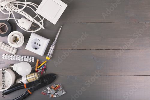 Poster electrical tools and equipment on wooden table with copy space