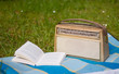 Buch und altes Transistorradio auf Picknickdecke