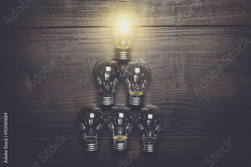 Poster glowing bulb leadership concept on brown wooden background