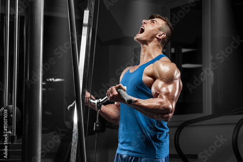fototapeta na ścianę Muscular man working out in gym doing exercises at biceps, strong male