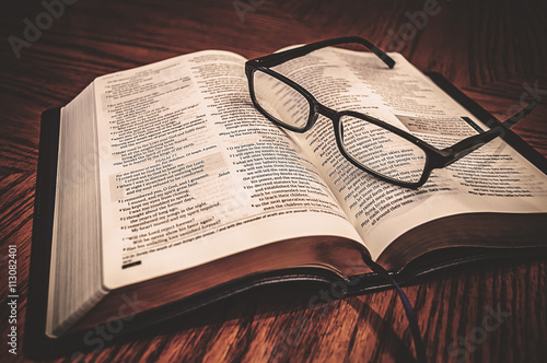 Open Study Bible On Table With Glasses Poster