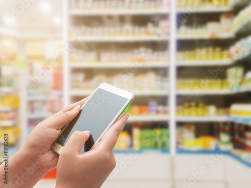 Papiers peints Pharmacie Women using smart phone on pharmacy