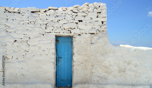 Old painted blue door on the whitewashed wall