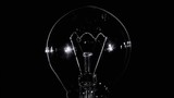Tungsten light bulb lamp blinking over black background, macro view, loop ready