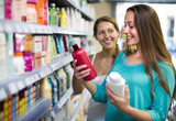 Woman choosing shampoo at store.