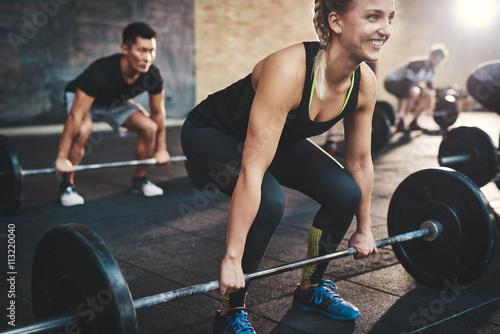 Kobieta wykonuje martwego dźwignięcia sztangi ćwiczenie