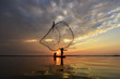 A fisherman casting a nets into the water during sunrise