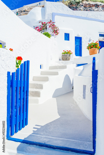 Zdjęcia na płótnie, fototapety na wymiar, obrazy na ścianę : Traditional architectural detail of Santorini street with whitewashed streets and blue gates, Greece