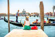 Quadro Young female traveler sitting on the pier and enjoying beautiful view on venetian chanal with gondolas floating in Venice