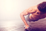 Fototapety Man doing push-up exercise with dumbbell. Strong male doing crossfit workout.