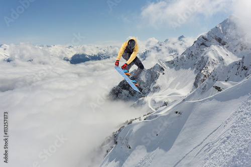 Poszter Snowboard rider jumping on mountains. Extreme freeride sport.