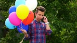 footage young man holding balloons and talking on smartphone